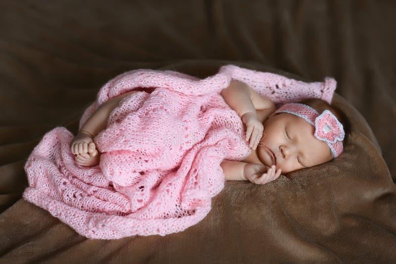 Menina recém-nascida que está dormindo lenço cor-de-rosa bonito, macio, coberto com as flores, as mãos e os pés, dedos pequenos imagens de stock