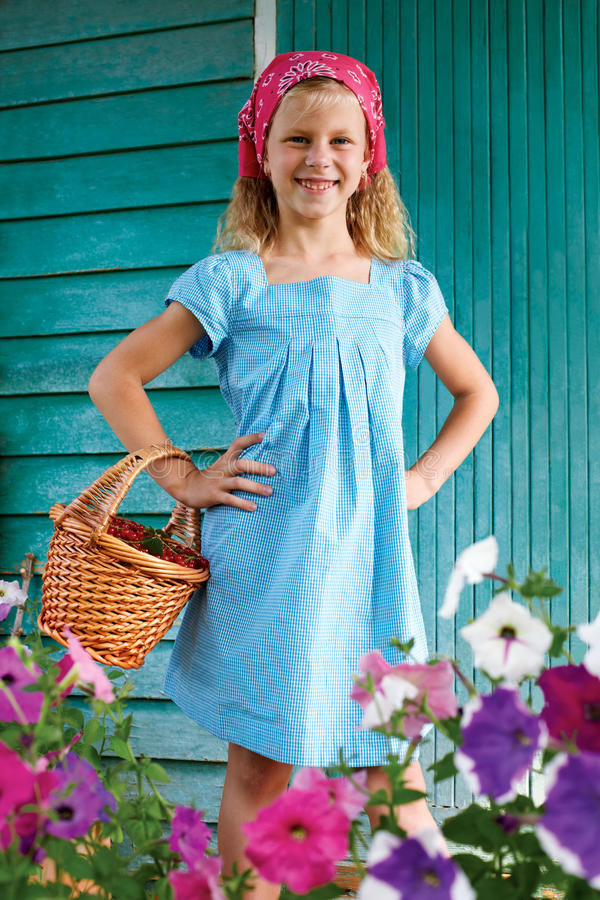A menina recolhe bagas do corinto vermelho em sua cesta fotografia de stock royalty free