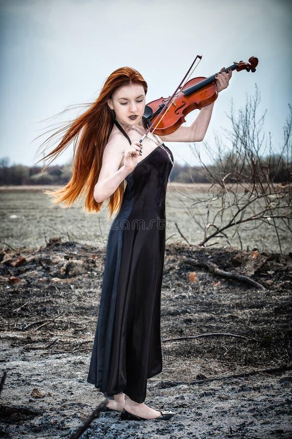 A menina red-haired com um violino fotografia de stock