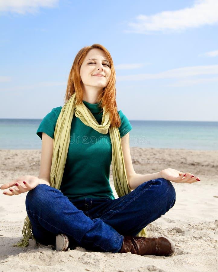 Menina Red-haired na praia no tempo de mola. imagem de stock