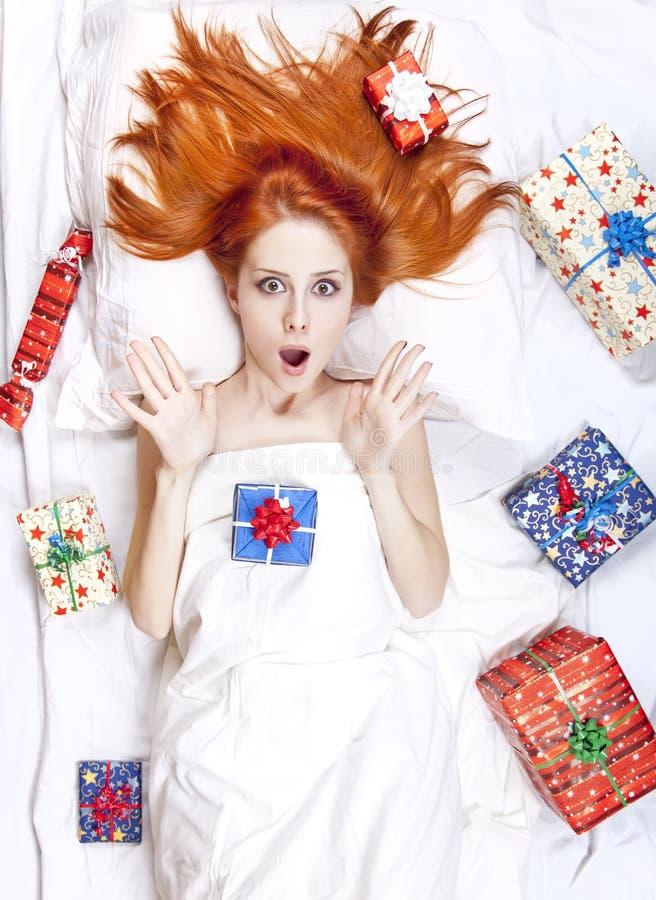 Menina red-haired surpreendida na cama com presentes. imagem de stock