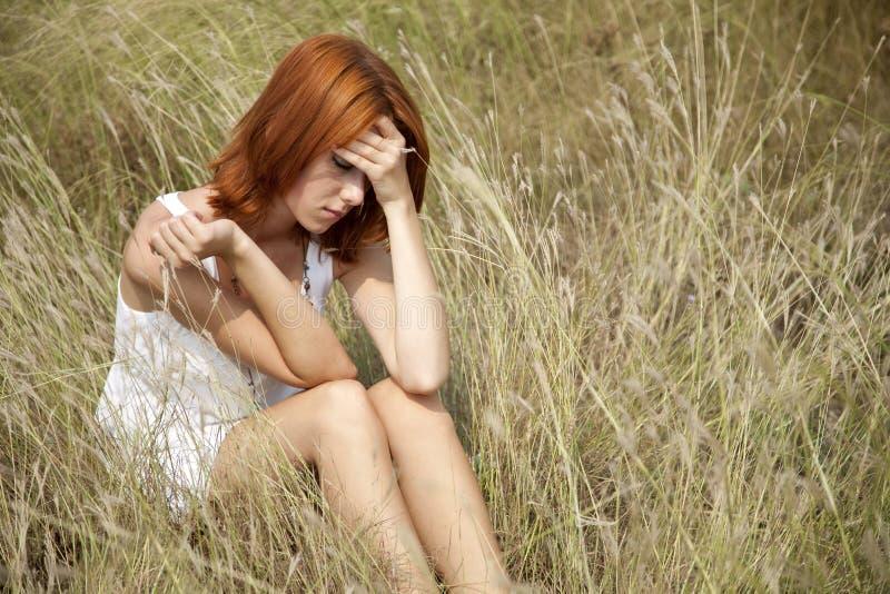 Menina red-haired triste na grama. imagens de stock royalty free