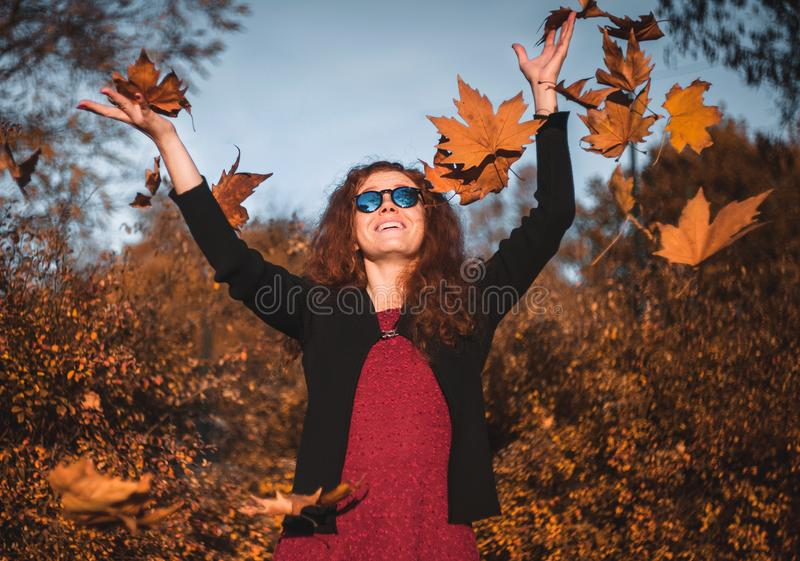 Menina redhaired bonita com folhas de queda fotografia de stock