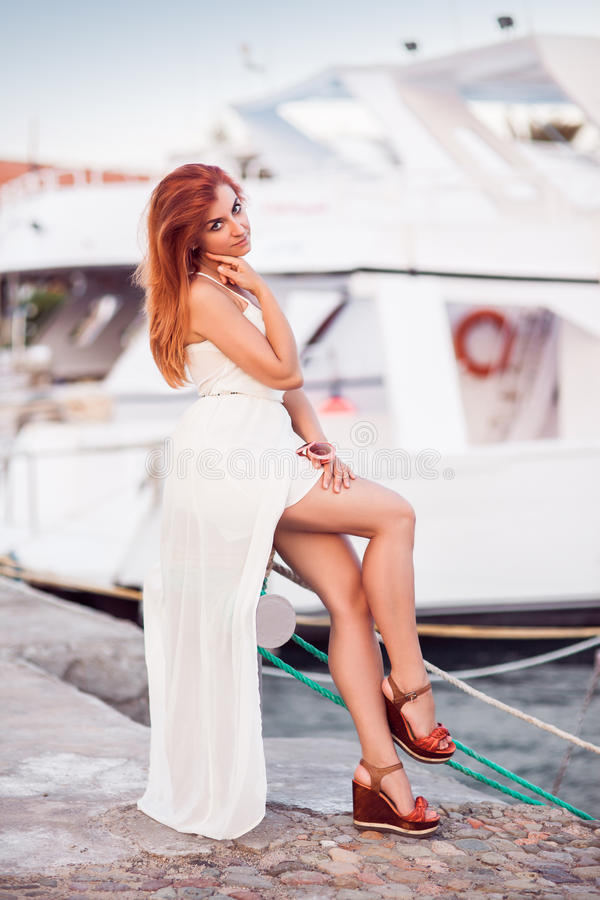 A menina redheaded atrativa caucasiano senta-se pelo beliche do iate imagem de stock royalty free