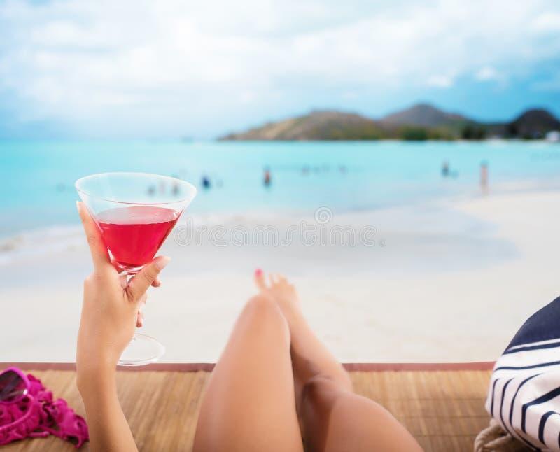 A menina relaxa na praia com uma bebida fria fotos de stock royalty free