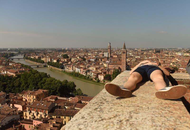 A menina relaxa perto do panorama de Castel San Pietro e de Verona com Adige foto de stock royalty free