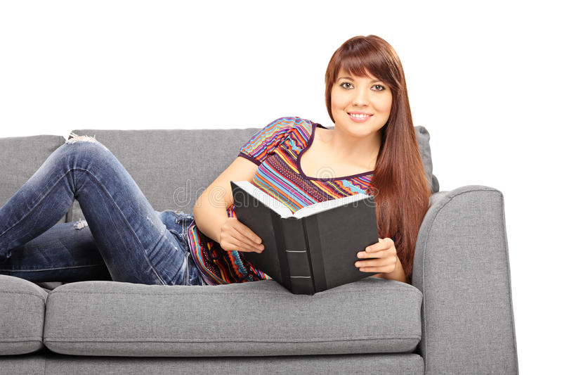 Menina relaxado que encontra-se no sofá e que guarda um livro imagens de stock