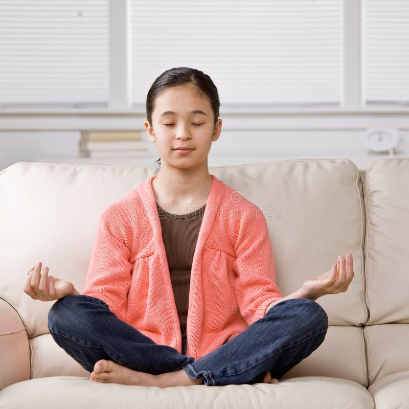 Menina Relaxed que senta de pernas cruzadas meditating fotos de stock royalty free