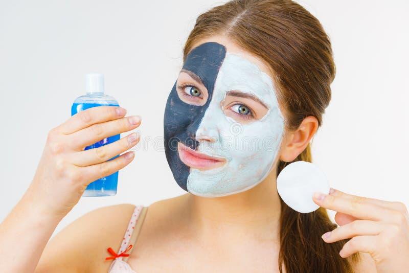 A menina remove a máscara branca preta da lama da cara foto de stock