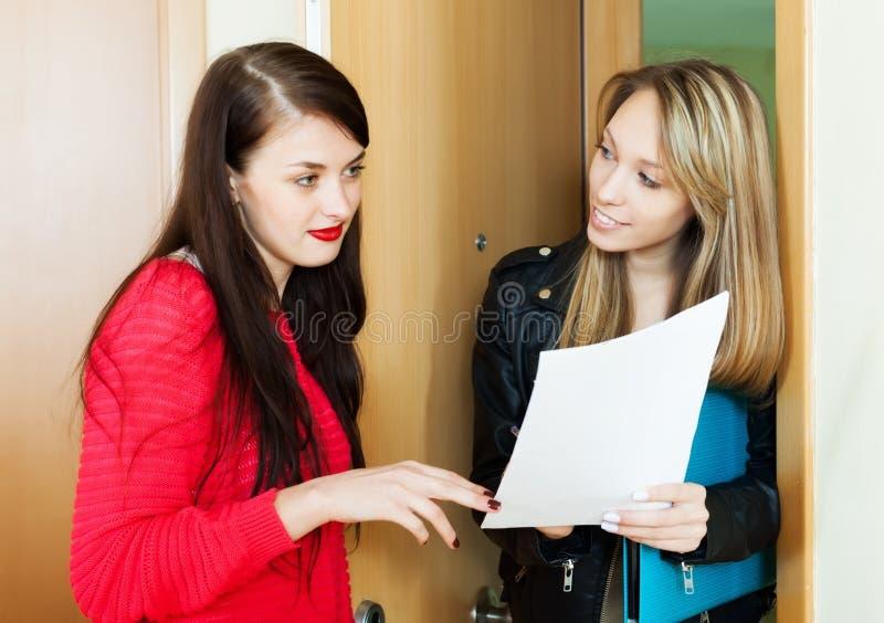 A menina responde a perguntas do visitante com papéis em casa fotos de stock royalty free