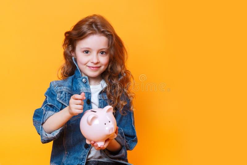 Menina respons?vel que p?e o dinheiro no mealheiro para a economia futura fotografia de stock