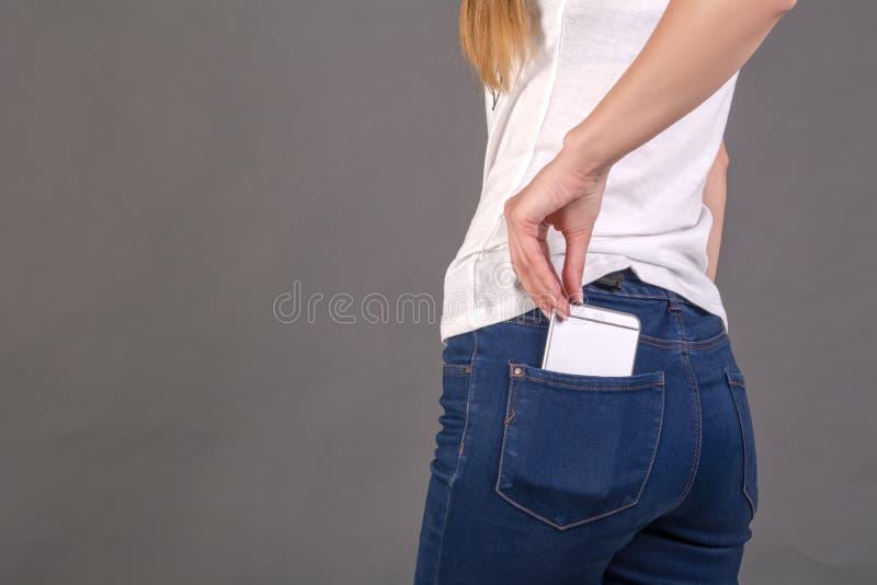 A menina retira o telefone celular do bolso traseiro das calças de brim imagem de stock