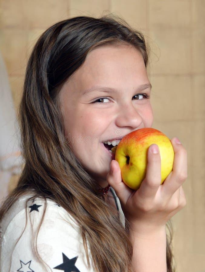 A menina ri e come a maçã imagem de stock royalty free
