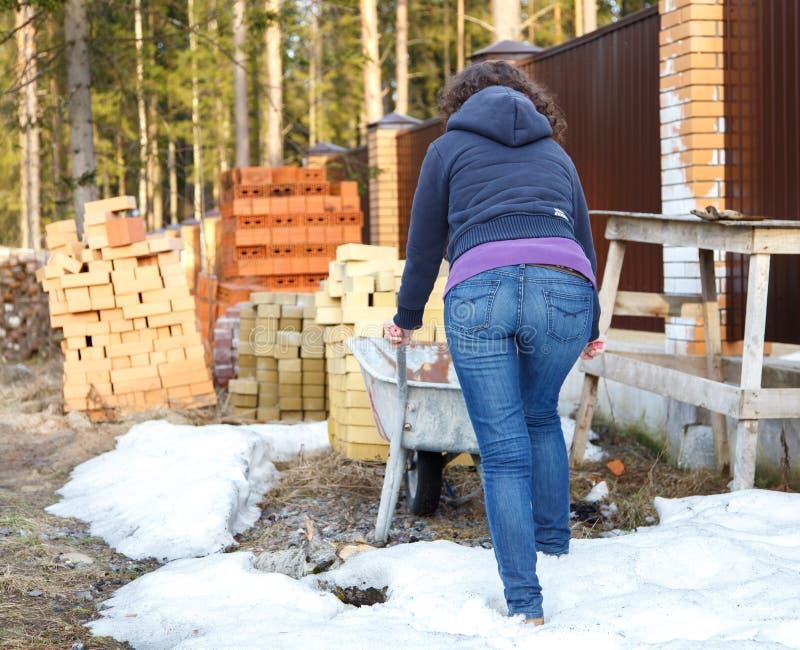 A menina rola o carrinho de mão aos tijolos no canteiro de obras fotografia de stock