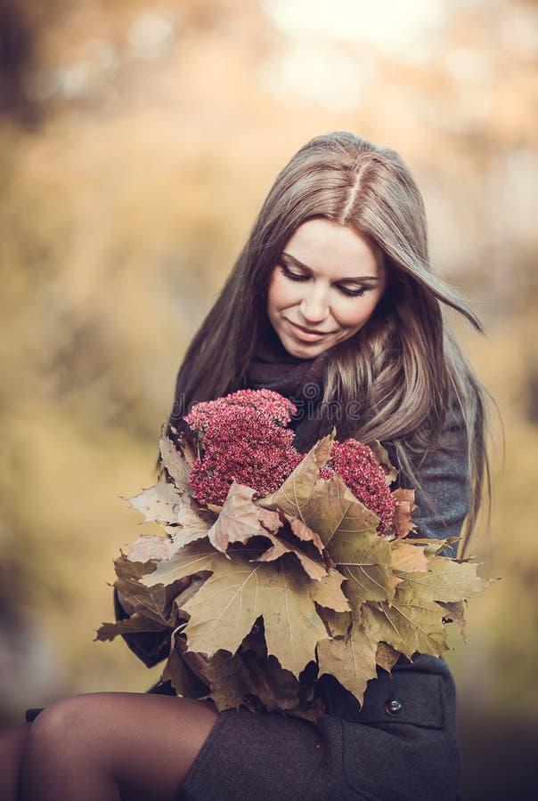 A menina romântica de sorriso com o ramalhete no outono estaciona imagens de stock