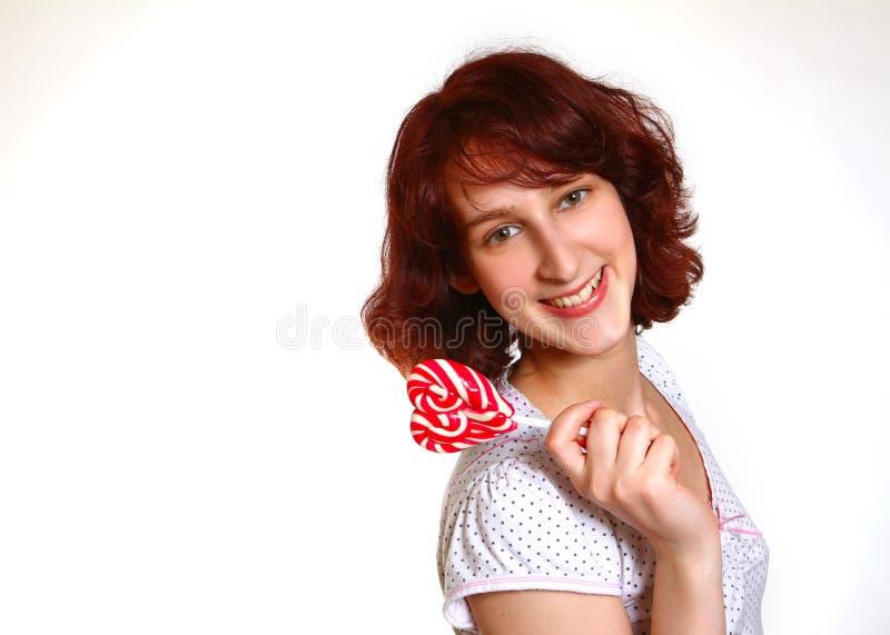 A menina romântica de sorriso com um pirulito no coração dá forma a o imagens de stock royalty free