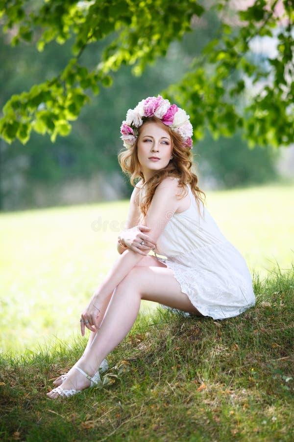 A menina romântica delicada em uma grinalda das peônias senta-se em um prado fotografia de stock