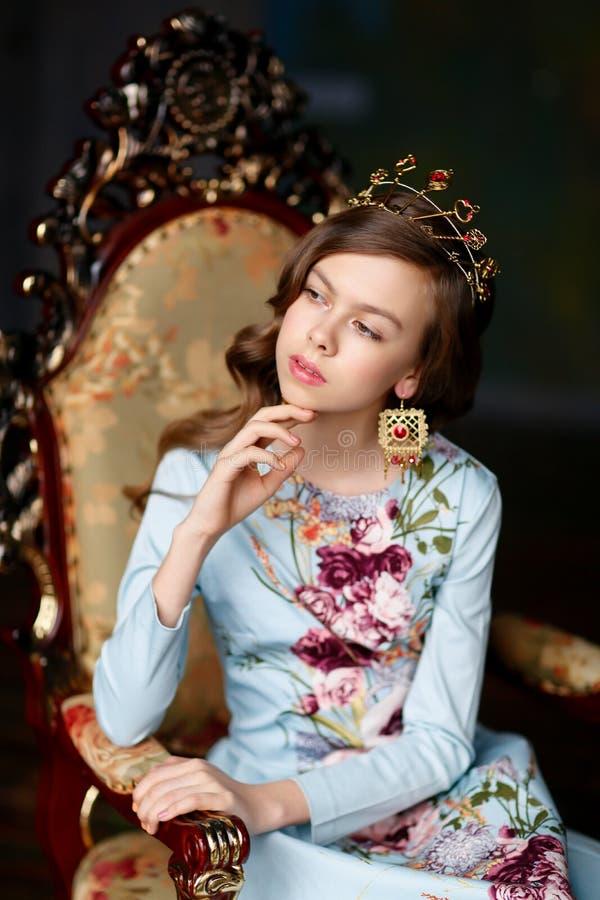 Menina romântica na coroa de brincos bonitos e do assento dentro foto de stock royalty free