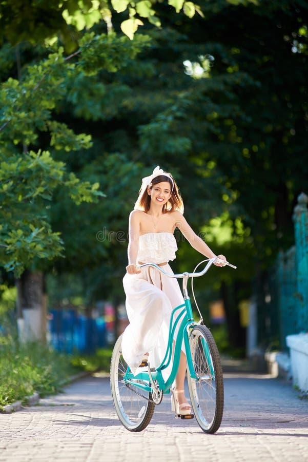 A menina romântica nos raios de luz solar monta na bicicleta retro imagens de stock royalty free