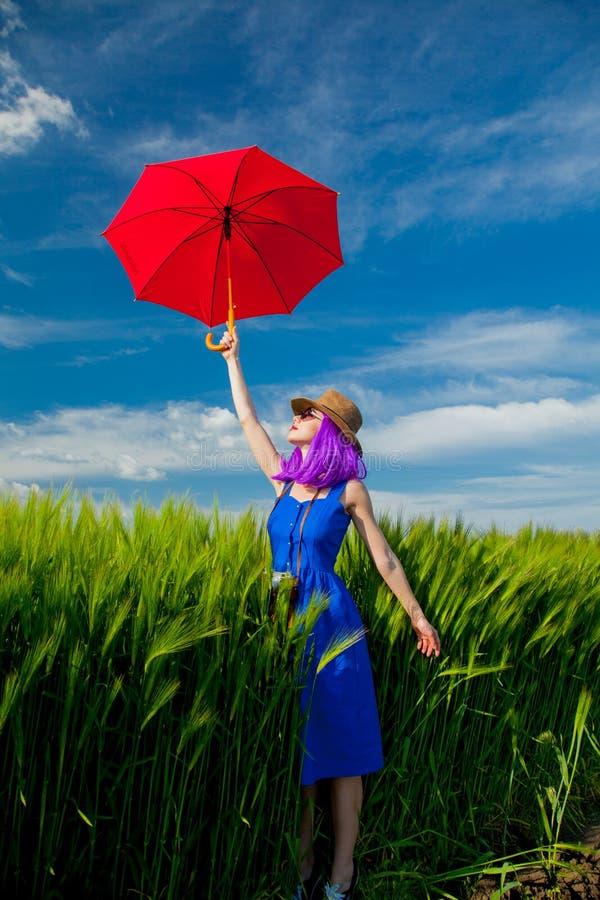 Menina roxa do cabelo com o guarda-chuva no campo de trigo imagens de stock royalty free