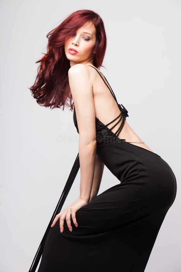 Menina ruivo atrativa no vestido longo do preto da noite fotografia de stock royalty free