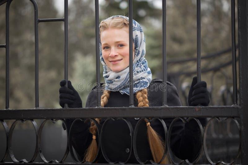 Menina ruivo bonita atrás da cerca forjada imagem de stock