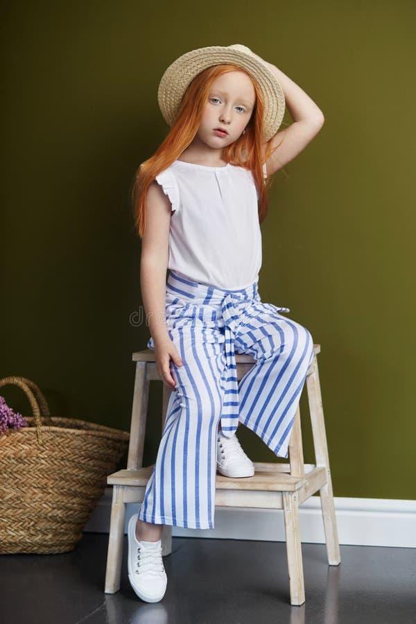 Menina ruivo bonita com cabelo longo e olhos azuis grandes bonitos Criança da menina do ruivo na roupa do verão que levanta no foto de stock