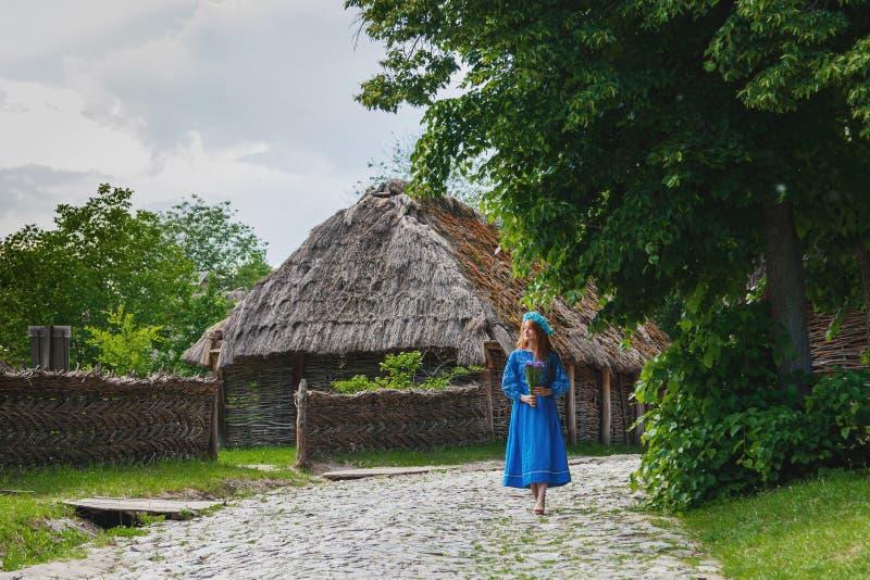 Menina ruivo bonita em um ucraniano azul do vestido com uma grinalda em sua cabeça fotos de stock royalty free