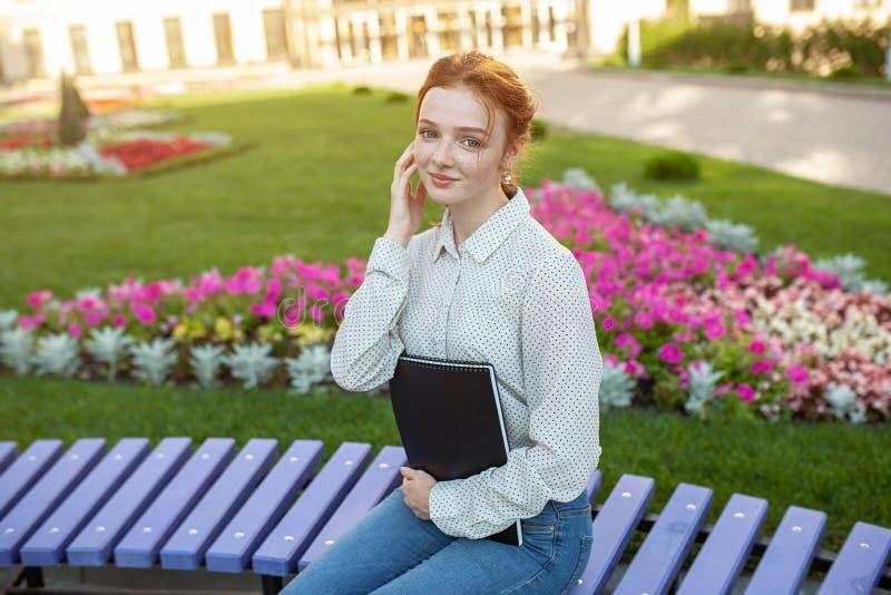 A menina ruivo bonita nova com as sardas que sentam-se em um banco perto da universidade guarda um caderno em suas mãos com traba foto de stock
