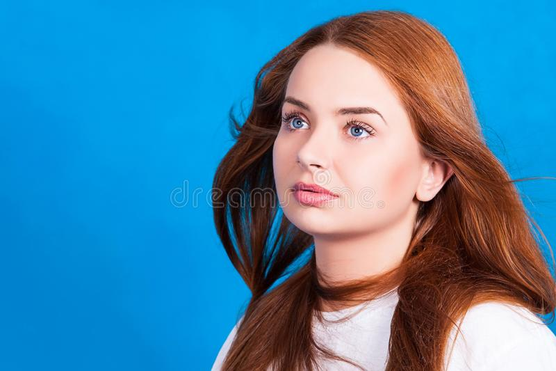 A menina ruivo bonita nova com o cabelo que torna-se no vento olha sonhadoramente para cima O tiro do estúdio, pele retoca fotos de stock