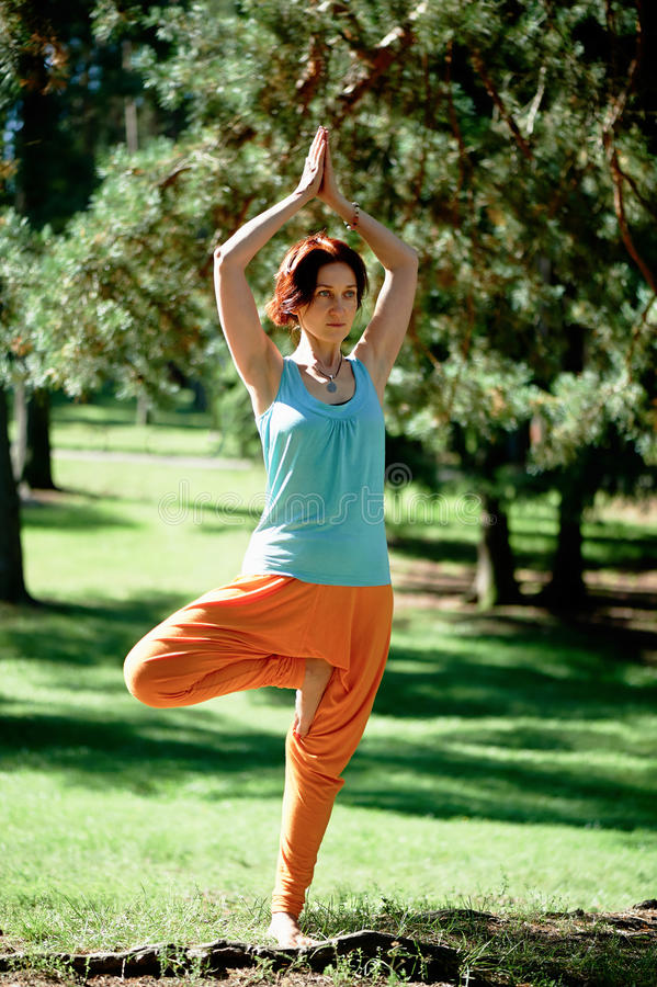 A menina ruivo bonita nova faz a ioga no parque no fundo verde imagem de stock