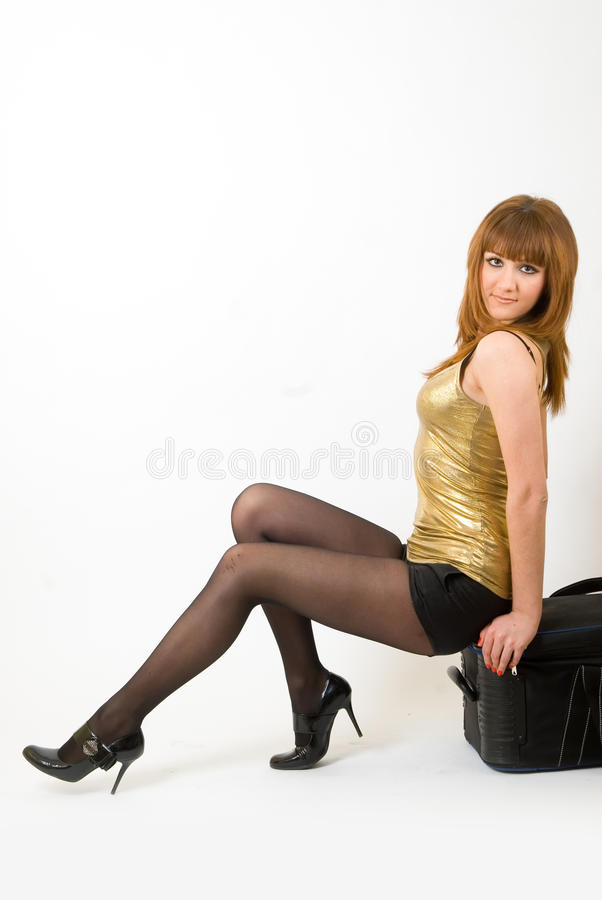 Menina ruivo bonita que senta-se na mala de viagem imagem de stock