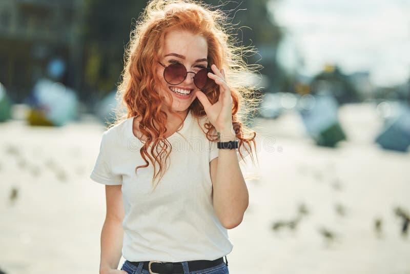 Menina ruivo bonita que tem o divertimento na rua As meninas têm uma figura bonita, um t-shirt branco e calças de brim com óculos fotos de stock royalty free