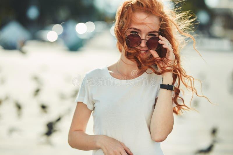 Menina ruivo bonita que tem o divertimento na rua As meninas têm uma figura bonita, um t-shirt branco e calças de brim com óculos fotografia de stock