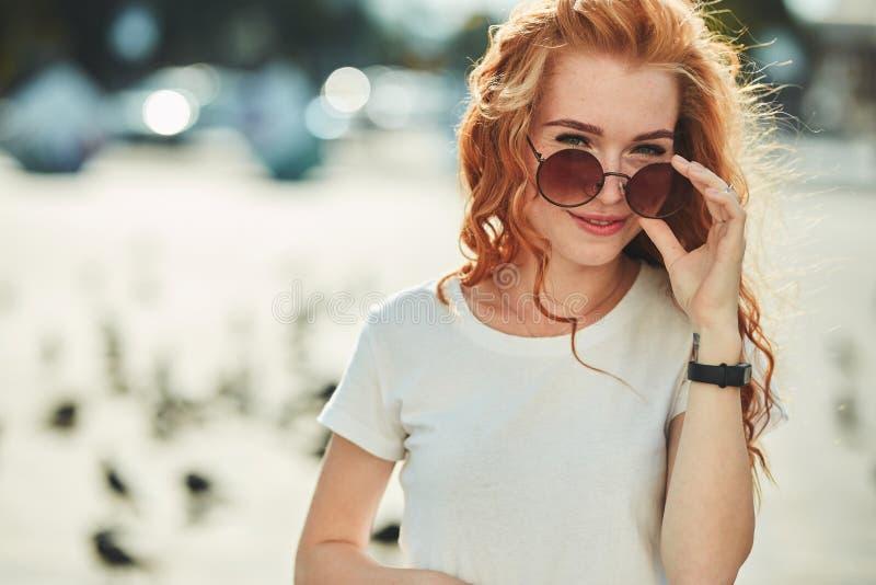 Menina ruivo bonita que tem o divertimento na rua As meninas têm uma figura bonita, um t-shirt branco e calças de brim com óculos imagens de stock royalty free