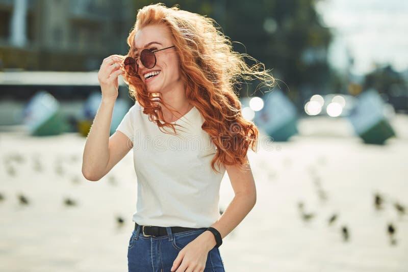 Menina ruivo bonita que tem o divertimento na rua As meninas têm uma figura bonita, um t-shirt branco e calças de brim com óculos imagem de stock