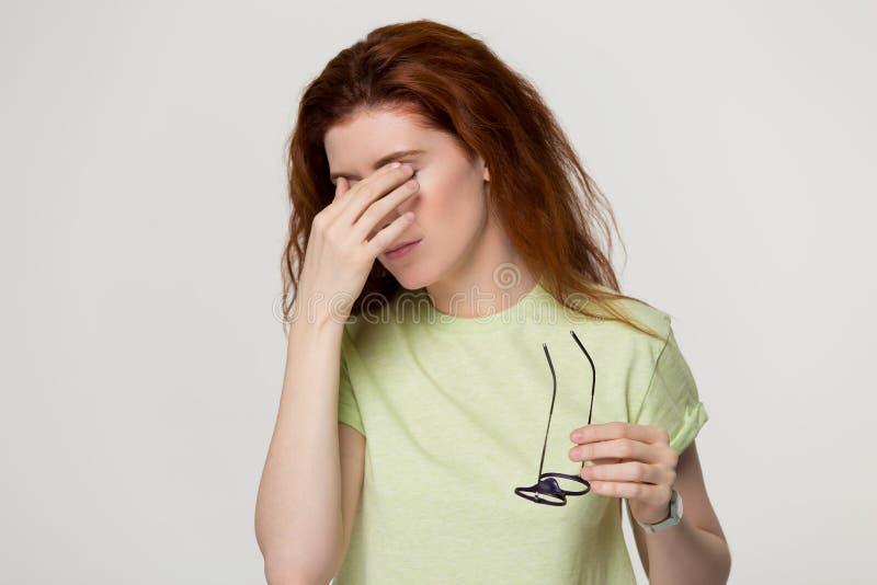 A menina ruivo cansada decola os vidros que sofrem dos problemas da vista fotos de stock royalty free