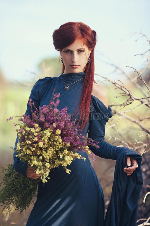Menina ruivo com um ramalhete de flores selvagens fotos de stock