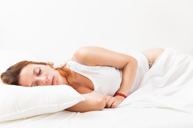 Menina ruivo da beleza que dorme no descanso branco na cama em casa fotografia de stock royalty free