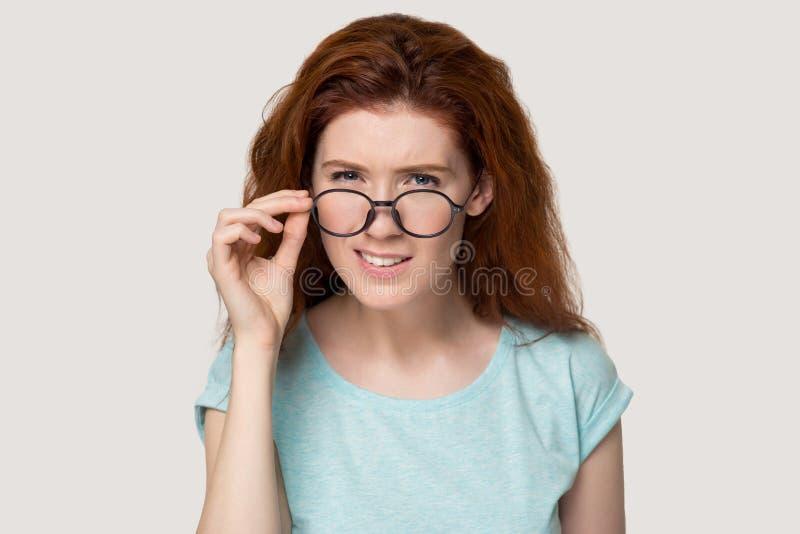 A menina ruivo duvidosa decola os vidros que sentem hesitantes fotografia de stock