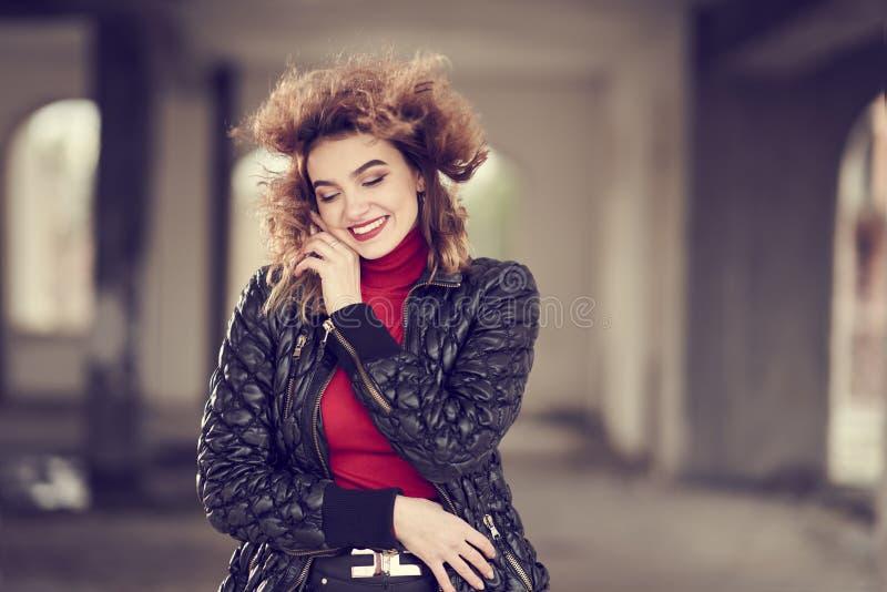 Menina ruivo elegante de sorriso com cabelo de fluxo nas calças de couro pretas, na camiseta vermelha e no revestimento preto lev fotos de stock