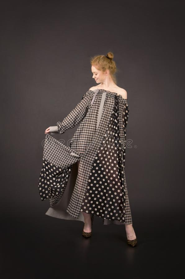 Menina ruivo em um vestido longo com ombros desencapados em um fundo escuro foto de stock
