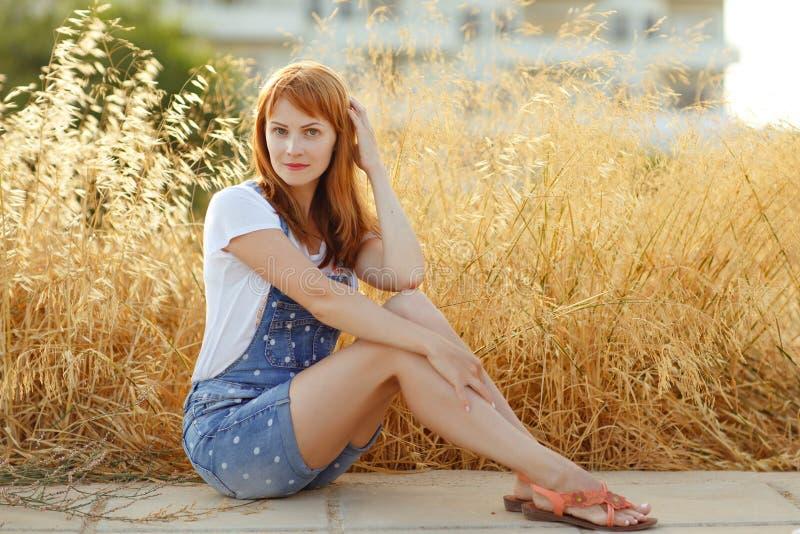 Menina ruivo encantador nos macacões da sarja de Nimes que sentam-se em um backgrou imagem de stock