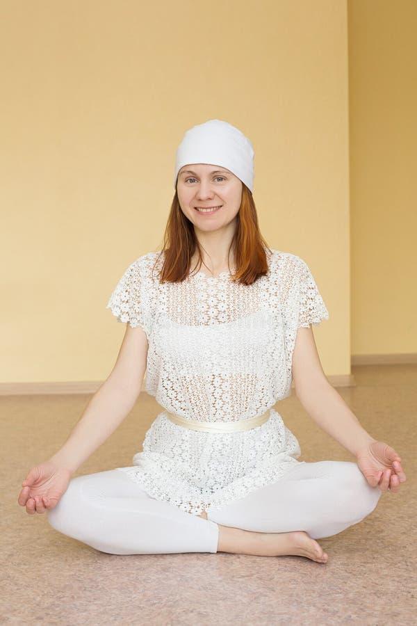 Menina ruivo na ioga praticando branca na posição de lótus foto de stock royalty free