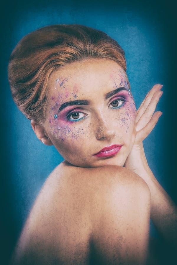 Menina ruivo nova bonita com um pulverizador da pintura em sua cara fotografia de stock