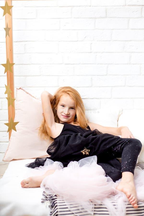 Menina ruivo nova bonita no vestido preto que encontra-se na cama fotos de stock