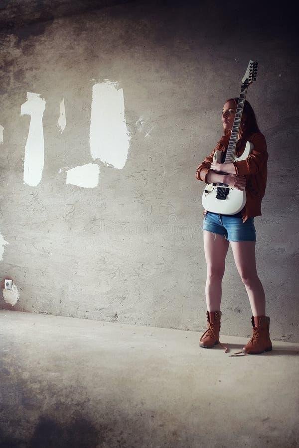 Menina ruivo nova com uma guitarra elétrica Gir do músico da rocha foto de stock
