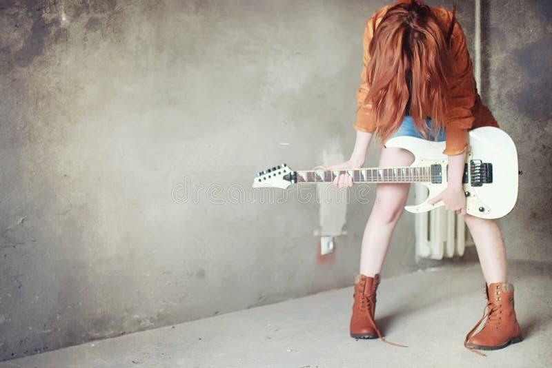 Menina ruivo nova com uma guitarra elétrica Gir do músico da rocha fotos de stock royalty free