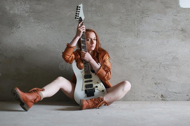 Menina ruivo nova com uma guitarra elétrica Gir do músico da rocha fotos de stock
