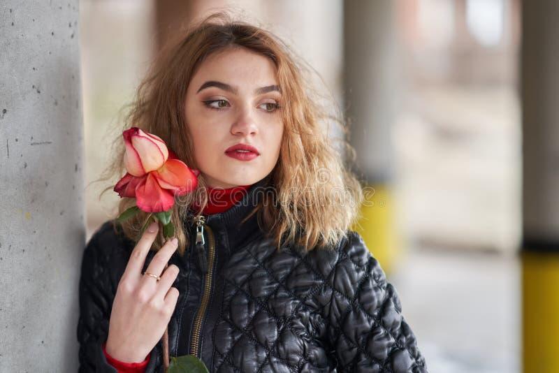 Menina ruivo nova em um revestimento preto que levanta com uma rosa vermelha em sua mão imagem de stock royalty free